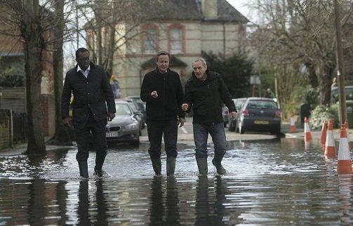 泰晤士河因河水猛涨导致部分河堤决堤,沿河地带形势严峻。首相卡梅伦(中)在泰晤士河畔视察灾区后表示,政府会尽全力救灾。