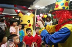 孩子們專注地看著小丑扭氣球,眼中寫滿了期待與好奇。