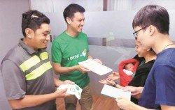 Grab司機法茲禮(左前)與周國康(右前)及林秀梅(右後)夫婦聚首,兩夫婦從GrabCar新加坡主管陳念輝(左後)手中接獲祝賀禮券。(Grab提供)
