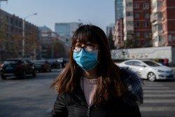 北京一名女市民戴著口罩出門,防範空氣污染影響健康。