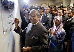 馬哈迪(左)為馬來西亞廉正研究院舉行的反貪研討會主持閉幕前,在該院牌匾上簽名。陪同包括副首相旺阿茲莎(右)、首相署部長劉偉強及阿布卡欣等人。