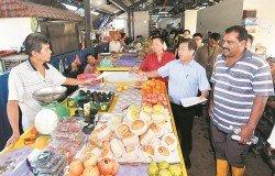 陳國偉(右2)派發吉隆坡市政局豁免執照及租金費用的通知信,予冷古斯路臨時巴剎小販。右起為峇蘭及李桂梁。