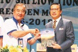 佘貴忠(左)贈送紀念刊物予廖中萊,感謝他為馬化合作社第39屆常年代表大會開幕。