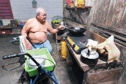 張運華坐在椅子上煮飯。