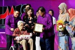 阿邦佐哈里(中)頒表揚獎狀予首批在砂州服務的護士吳金蘭(譯音,左)。