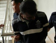 被告週三被带上法庭时低头避开镜头。
