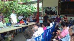 周忠信(左站者)出席君隆南峇村村民對話會,承諾將把村民訴求帶上官方討 論,盡快尋求和平方案解決村內基建問題。
