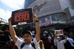 政府欲簽署《消除一切形式種族歧視國際公約》,引起馬來穆斯林反彈,圖為參與本月4日舉行反《消除一切形式種族歧視國際公約》集會的集會者,手持反對的大字報。