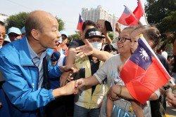 國民黨高雄市長候選人韓國瑜(左)周三在高雄市進行車隊掃街拜票,不少支持者爭相與他握手。