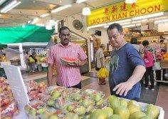 葉學光(右)能用流利的泰米爾語和顧客介紹和推薦水果, 令許多顧客感到驚訝。