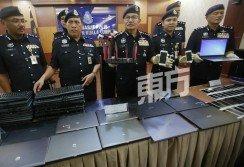 瑪茲蘭(中者)和一眾建功的 警員,向媒體記者展示警方在 行動中起獲的電腦器材。(攝影:駱曼)