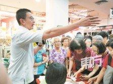 領取購物券的人潮爭先恐后, 鄧章欽 (左)耐心勸告受惠者遵守秩序。(攝影:陳慧蕓)