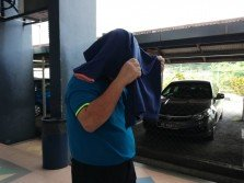 被告步入法庭時,以衣物遮掩樣貌。