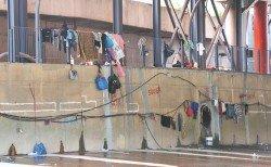 流浪漢將衣物和個人用品掛在河堤牆壁上的圍欄和電線,有礙市容,也造成一定的危險。