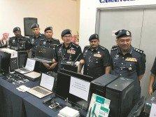 瑪茲蘭(左4)在建功警員的陪同下,向媒體記者展示警方所 起獲的電子產品。