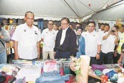 阿邦佐哈裡(中)為跳蚤市場主持開幕后,參觀該市場攤位。