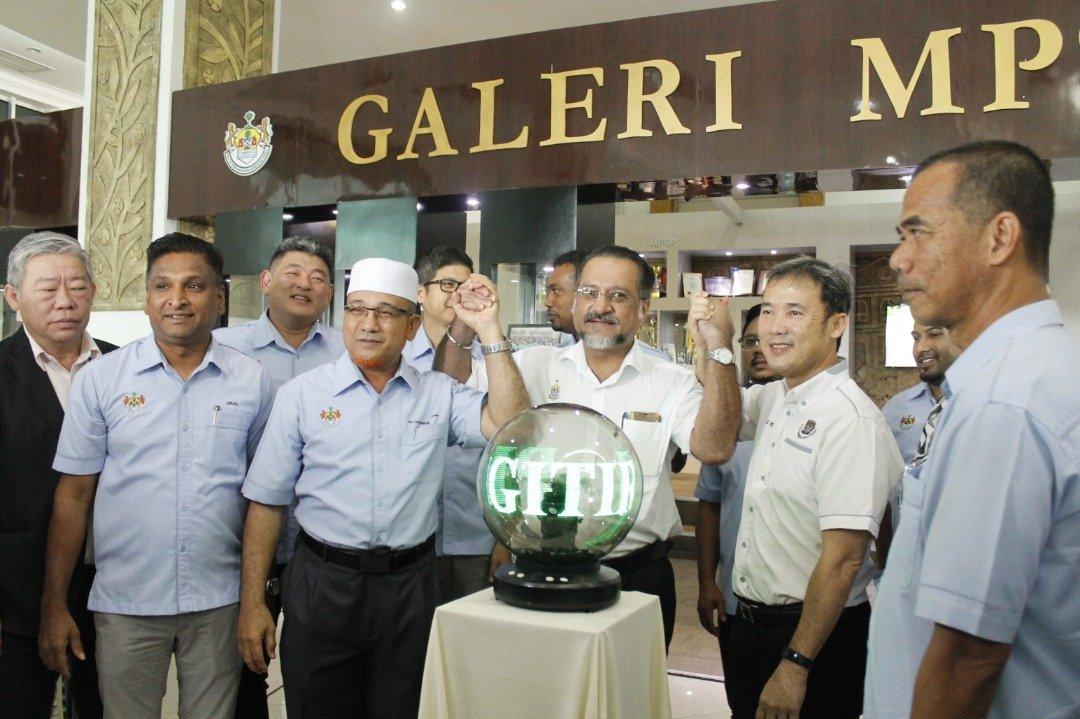 """佳日星(左4)举起罗查理(左3起)和尤端祥的手,宣布威省市政局已获得内阁批准升格为""""市""""。"""