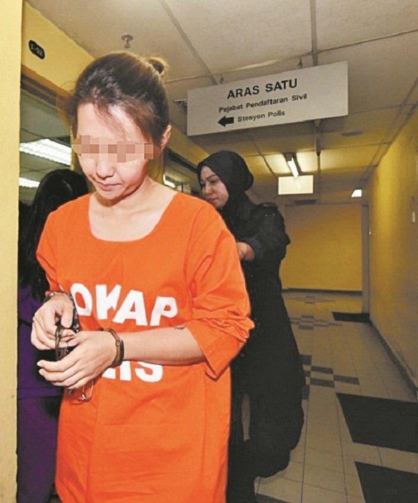女嫌犯一直低头,迴避摄影镜头。