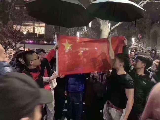 墨尔本中国留学生包围港独人士,齐唱国歌雨中为国旗撑伞。
