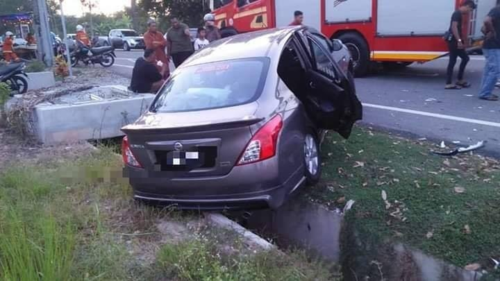 另一辆轿车被对面的四轮驱动车撞及,后车轮卡在沟渠。