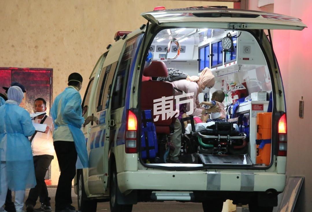 一名母亲安抚准备被送往医院的孩子。(摄影:刘维杰)