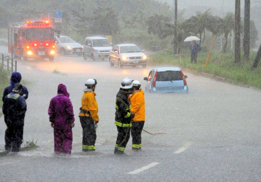 洪水淹没了道路低洼区,导致交通工具无法继续前行,一辆轿车更是被洪水包围。而受困在一旁的民众,正等待前来的消防人员施予救援。