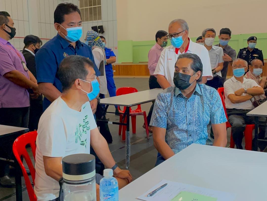 凯里(坐者右)向民众了解接种新冠疫苗的情况。