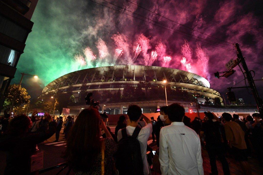 绚丽夺目的烟花周日晚照亮东京国立竞技场上空,为2020残奥会画下句点,而许多民众同时在场馆外观赏烟花。(图取自法新社)
