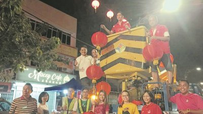 直落拿督社区服务中心团队协助在仁嘉隆大街悬挂红灯笼,增添新年气息,上中为欧阳捍华及上左为郑永德。