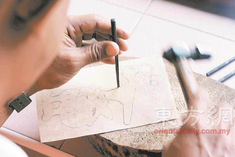 皮影玩偶制作师使用木槌和凿子,一点点凿出不同形状,形成镂空。