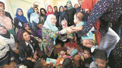 旺阿兹莎(中)周六访问彭亨卡宋苏丹后儿童之家,看到小孩时非常开心。