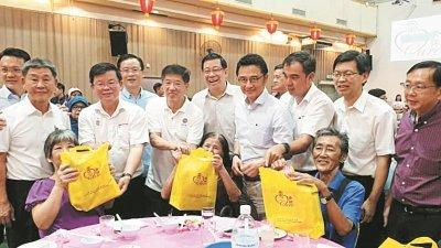 曹观友(左3)在杨顺兴(左起)、方炎华、陈国平、祝友成、戴良业、孙意志、鲁世巍陪同下,分发日常用品予乐龄人士。
