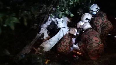 闻讯而来的消拯人员合力将被夹毙在车内的两名死者遗体移出。