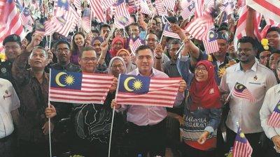陆兆福(右3)出席国庆日活动时,与学生们一起高举大马国旗。