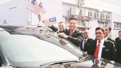 郑国球(右2)为轿车贴上国旗旗帜,右为慕斯达法。