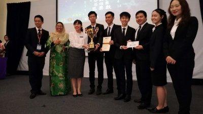 张念群(左3)颁发冠军杯给马来亚大学辩论队。左起为杨鸿洲及杜丽莎。
