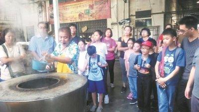 汪永平(炉前)向游客示范传统炭烧马蹄酥的制作过程,而游客也观赏得津津有味。