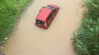 一辆红色国产迈薇轿车掉入河中,幸好女司机安全脱困。