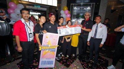 罗兹兰(右2)迎接吉隆坡塔2019年第100万名游客,并移交礼品给幸运儿哈基米(左3)。右为莫哈末祖菲嘉里。