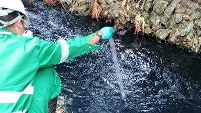森州环境局官员收集受污染的河水样本,以送往化验局进行检验。