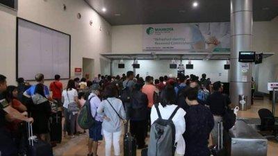 在马六甲峇株安南国际机场准备飞往槟城的乘客排队等待消息。(图片取自网络)