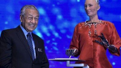 机器人索菲亚(右)在峰会上与敦马哈迪展开风趣对话,并现场绘制敦马肖像,展现类人机器人的强项。