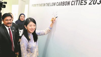 杨美盈(右)为2030年低碳城市挑战主持推介后,在看板上签名。左为赛阿曼。