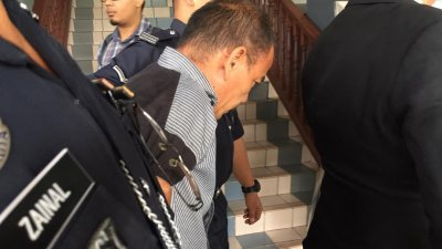 再纳阿比丁(左2)被警方带离法庭时,低头避开镜头。