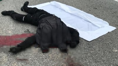 车祸发生后,断头惨死的新加坡籍摩哆骑士倒卧在马路中央,斑斑血迹让人触目惊心。(图由警方提供)