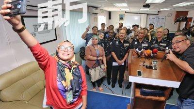 莫哈末卡立尔(警方制服右2)将升任武吉安曼肃毒组总监,记者向他表达依依不舍之情,并与他自拍留念。(摄影:刘维杰)