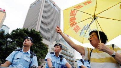 大批示威者周一下午到香港特首办门外聚集,要求特首撤回《逃犯条例》,这是其中一名女示威者撑著特制黄色雨伞高呼口号,有多名警察在场戒备。