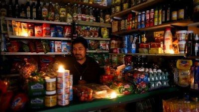 由于电力互联系统瘫痪,导致阿根廷周日全国大范围停电。一名在阿根廷首都布宜诺斯艾利斯经营杂货店的民众,于停电期间点燃蜡烛,并在微弱的火光下继续营业。