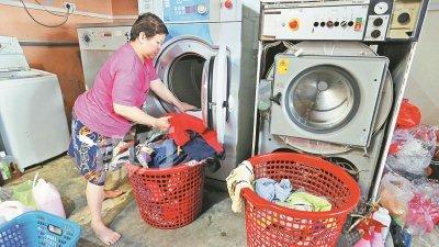 林宝珠需要扶靠著洗衣机,才能将衣服放入洗衣机。
