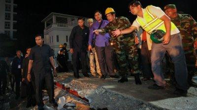 柬埔寨首相洪森(右3)周日穿上军装到塌楼处视察,并参与救援工作,与现场官员研究施救方法。